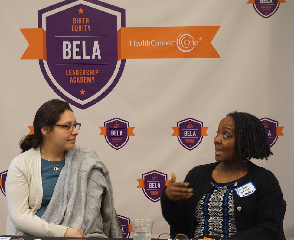 Women speaking in front of BELA birth equity leadership academy banner
