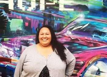 Esperanza Dodge against car mural backdrop