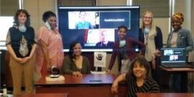 women gathered in a conference room in front of large screen at training