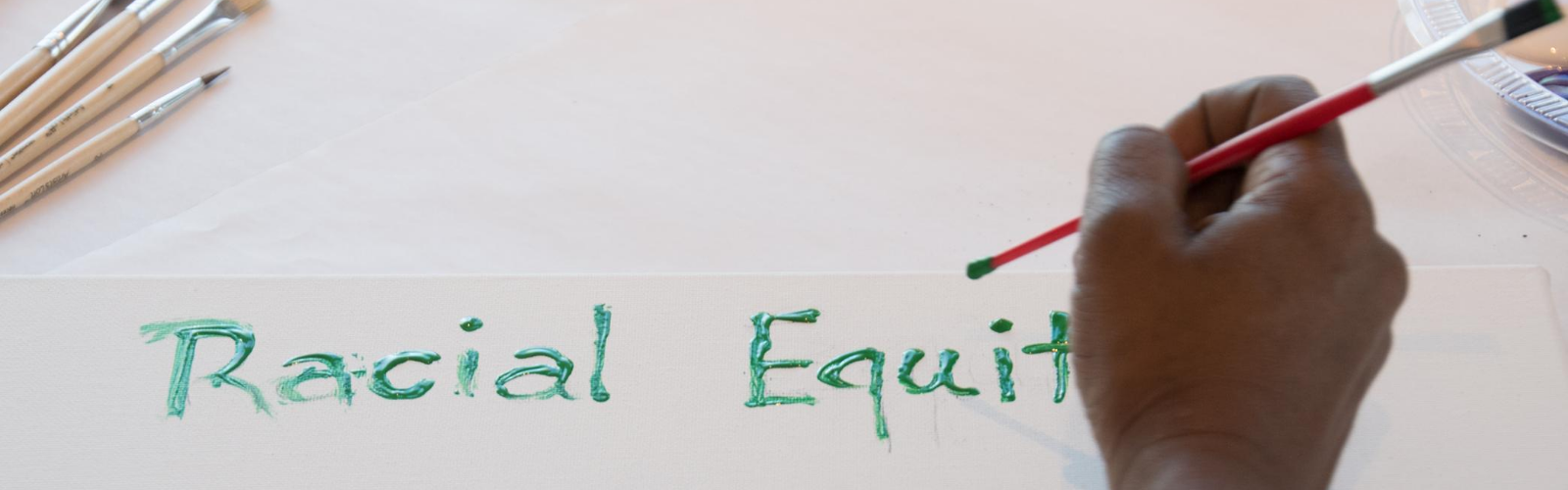 woman painting the words racial equity
