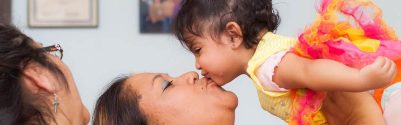 woman kissing a baby in the air while a doula looks on