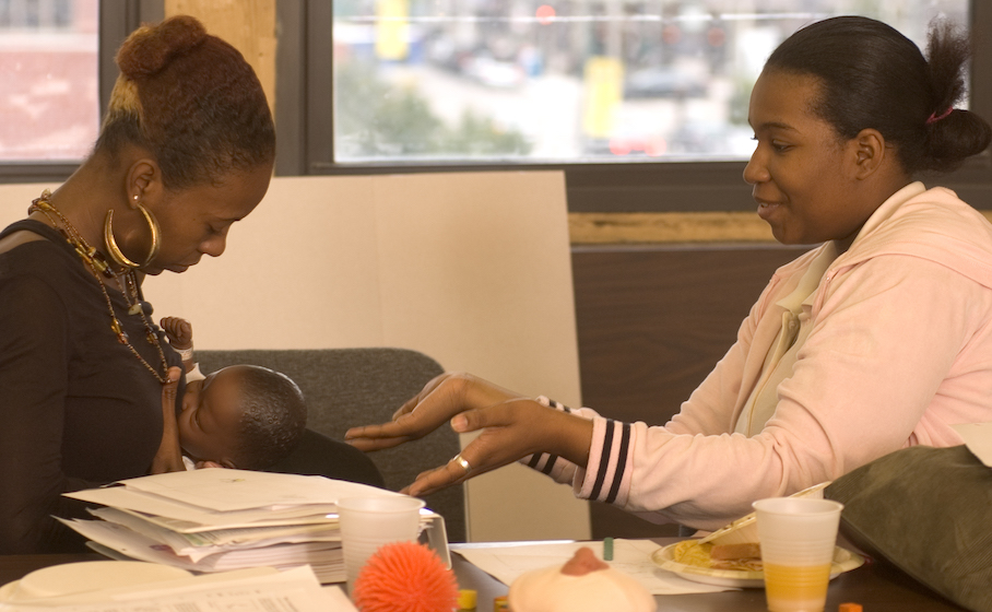 Black doula coaching a Black woman on how to breastfeed in office setting